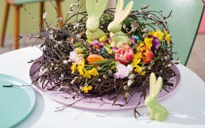 Stilvolles Osternest mit frischen Blumen als Tischdeko