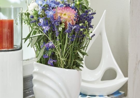 Fensterdeko für den Sommer mit frischen Blumen und Boot